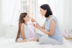 La foto de la hembra joven morena atractiva sostiene la botella de crema, la aplica en la piel de la hija, tiene expresiones posi imágenes de archivo libres de regalías