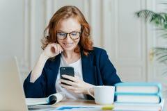La foto de la hembra preciosa se sienta con el dispositivo del smartphone, tipos reacción, trabaja en oficina en el ordenador por foto de archivo