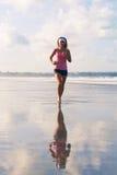 La foto de la muchacha de los deportes se ejecuta a lo largo de la playa Fotos de archivo libres de regalías