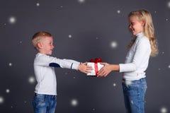 La foto de la Navidad del pequeño muchacho hace una sorpresa a la muchacha hermosa, la dejó nevar, da un caja-regalo Imagenes de archivo