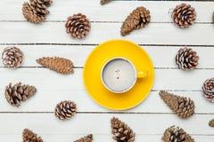 La foto de la taza de café amarilla cerca secó conos hermosos en Fotografía de archivo libre de regalías