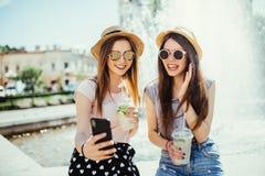 La foto de las dos mujeres contentas de la raza mixta consigue buenas noticias en el teléfono móvil, recibe el correo electrónico foto de archivo libre de regalías