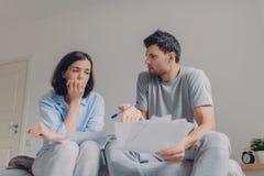 La foto de los pares jovenes agotadores de la familia tiene muchas deudas, prepara informe fincial, piensa en convertirse del fut imagen de archivo libre de regalías