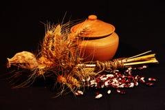 La foto de los platos de la arcilla con la amapola y el trigo secos foto de archivo