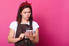 La foto de la muchacha pensativa con el delantal marrón manchado con la harina, sostiene el artilugio a disposición e intenta enc imagen de archivo