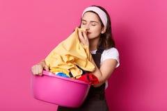 La foto de la mujer atractiva joven que trabaja en casa, lleva la camiseta, el delantal marrón y la banda del pelo, colocándose c fotografía de archivo libre de regalías