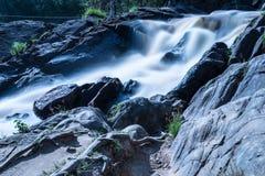 La foto de la pequeña cascada o catarata en el bosque taked en el día de verano soleado caliente con la exposición larga foto de archivo libre de regalías