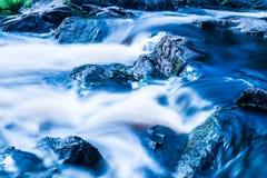 La foto de la pequeña cascada o catarata en el bosque taked en el día de verano soleado caliente con la exposición larga imagen de archivo