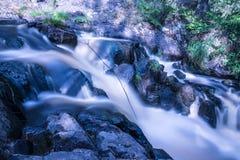 La foto de la pequeña cascada o catarata en el bosque taked en el día de verano soleado caliente con la exposición larga fotografía de archivo