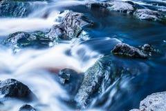 La foto de la pequeña cascada o catarata en el bosque taked en el día de verano soleado caliente con la exposición larga fotos de archivo libres de regalías