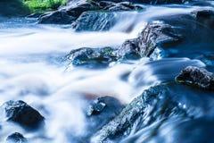 La foto de la pequeña cascada o catarata en el bosque taked en el día de verano soleado caliente con la exposición larga imagen de archivo libre de regalías