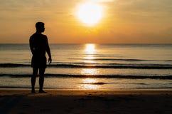 La foto de la silueta de un hombre que se coloca solamente en la playa disfruta del momento de la salida del sol foto de archivo libre de regalías