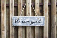 La foto de la tabla de madera con el ` de las letras sea nuestro ` de la huésped en el fondo de madera imagen de archivo