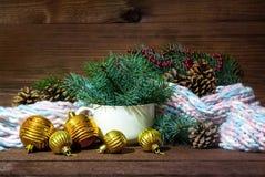 La foto de la taza blanca con el Año Nuevo de la rama, de la bufanda y del oro del abeto juega en el fondo de madera Imágenes de archivo libres de regalías