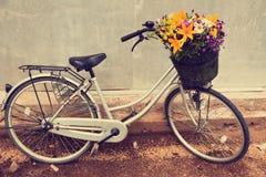 La foto de una bicicleta con una cesta llena de campo florece Fotos de archivo