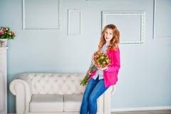La foto de una muchacha hermosa en una chaqueta rosada y tejanos en la primavera adornó el interior de la casa Imagenes de archivo