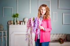 La foto de una muchacha hermosa en una chaqueta rosada y tejanos en la primavera adornó el interior de la casa Imagen de archivo libre de regalías
