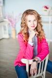La foto de una muchacha hermosa en una chaqueta rosada y tejanos en la primavera adornó el interior de la casa Fotos de archivo libres de regalías