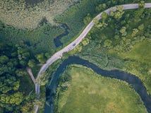 La foto del abejón de la conducción de automóviles en el camino por el río debajo de los árboles, remata abajo de la visión en la imagenes de archivo