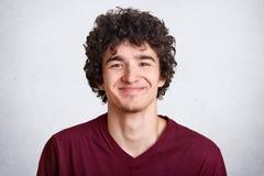 La foto del individuo sin afeitar hermoso mira con la expresión agradable directamente la cámara, lleva la camiseta marrón de mod imagen de archivo