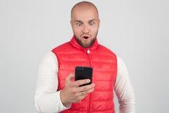 La foto del maschio sgomento legge il messaggio di testo con l'espressione sorpresa, tiene il telefono cellulare, scopre qualche  immagini stock