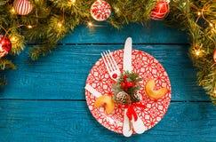 La foto del pino si ramifica, piatti con il modello rosso, biscotti di previsione, forcella, coltello, decorazione di Natale Fotografia Stock Libera da Diritti