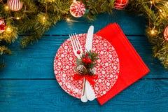 La foto del pino si ramifica, piatti con il modello rosso, forcella, coltello, decorazione di Natale, tovagliolo Fotografie Stock