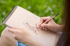 La foto del primo piano della donna passa il disegno con la matita Fotografia Stock Libera da Diritti