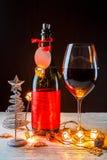 La foto del ` s del Año Nuevo de la botella con la cinta roja, árbol de navidad juega, copa de vino Foto de archivo libre de regalías