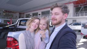 La foto del selfi de la familia en el centro auto, padres con la muchacha linda del niño con llaves toma la foto del selfie en el almacen de video