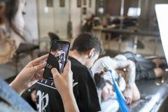 La foto del teléfono celular de un hombre joven tatuó el tatuaje de una cabeza del ` s del hombre fotografía de archivo