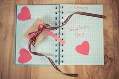 La foto del vintage, día de tarjetas del día de San Valentín escrito en cuaderno, envolvió el regalo y corazones Imagen de archivo libre de regalías