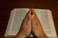 La foto del vintage de la mano con la biblia que rogaba, manos dobló en el rezo en una Sagrada Biblia, Jesus Christ imágenes de archivo libres de regalías