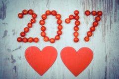 La foto del vintage, el Año Nuevo 2017 hizo de viburnum rojo y de corazones de madera rojos en viejo fondo de madera Imagen de archivo libre de regalías
