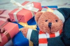 La foto del vintage, el oso de peluche con los regalos coloridos para la Navidad o la otra celebración Fotografía de archivo