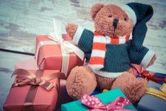 La foto del vintage, el oso de peluche con los regalos coloridos para la Navidad o la otra celebración Imágenes de archivo libres de regalías