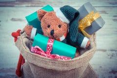 La foto del vintage, el oso de peluche con los regalos coloridos para la Navidad o la otra celebración Foto de archivo