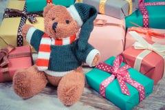 La foto del vintage, el oso de peluche con los regalos coloridos para la Navidad o la otra celebración Imagenes de archivo