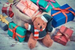La foto del vintage, el oso de peluche con los regalos coloridos para la Navidad o la otra celebración Foto de archivo libre de regalías