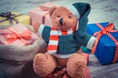 La foto del vintage, el oso de peluche con los regalos coloridos para la Navidad o la otra celebración Imagen de archivo libre de regalías
