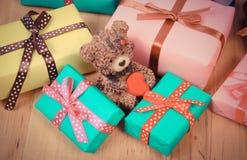 La foto del vintage, el oso de peluche con los regalos coloridos para la Navidad o la otra celebración Fotografía de archivo libre de regalías