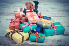 La foto del vintage, el oso de peluche con los regalos coloridos para la Navidad o la otra celebración Fotos de archivo