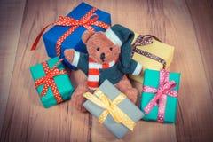 La foto del vintage, el oso de peluche con los regalos coloridos para la Navidad o la otra celebración a bordo Fotografía de archivo