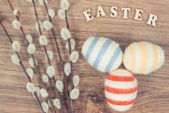 La foto del vintage, la inscripción Pascua, los amentos y los huevos envolvieron la secuencia de lana en el tablero rústico, deco Imagen de archivo
