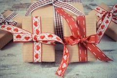 La foto del vintage, los regalos envueltos en el papel reciclado para las tarjetas del día de San Valentín o la otra celebración Foto de archivo