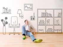 La foto dell'uomo che si siede sul pavimento con il fiore dipinto della casa, pitture sulla poltrona della parete, accantona, lib Fotografia Stock