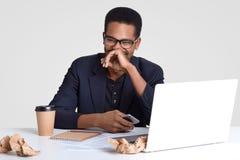 La foto dell'uomo pelato scuro positivo vestito in vestiti convenzionali, felici di leggere il messaggio di testo divertente, tie immagine stock libera da diritti