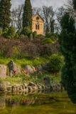 La foto della chiesa vicino al piccolo lago con i tulipani in primavera condisce Fotografia Stock