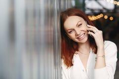 La foto della donna adorabile con capelli rossastri, sorriso positivo, ha conversazione con il cliente, chiamate del telefono all immagini stock