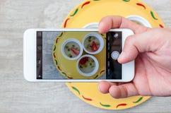 La foto della fragola della frutta ed il kiwi gelatinizzano il dessert tramite lo smartphone Immagine Stock Libera da Diritti